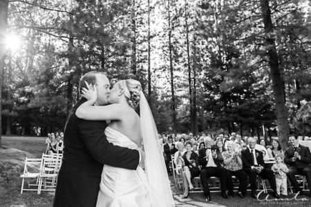 bride and groom kissing in front of guests