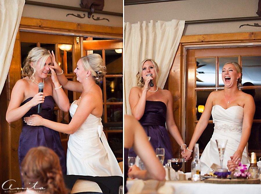 bride and bridesmaid laughing and crying together at wedding reception