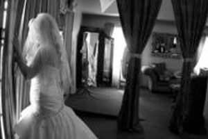 bride standing near the window looking outside