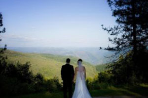 bride and groom standing on the mountain hill